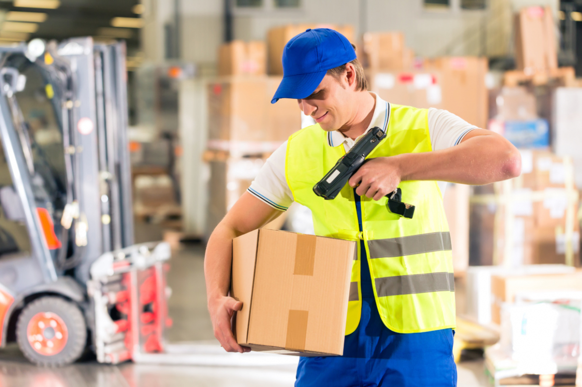 Logisitics - worker scans package in warehouse of forwarding