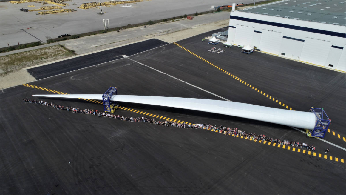 LM Wind Power employees next to a wind turbine blade